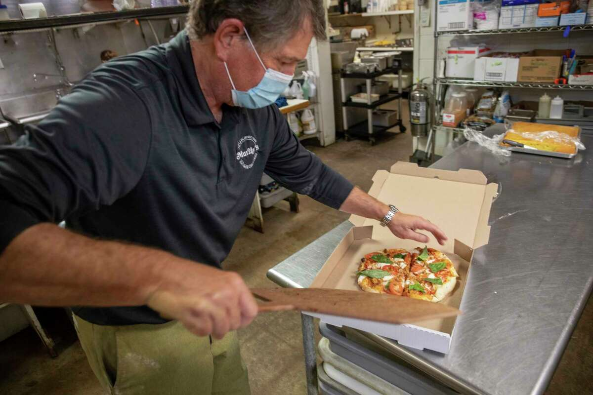 Murray's Deli is adding wood fired brick oven pizza to the menu in February. Scott Dufford slides a Dufford Classic pizza in a take-out box Thursday, Jan. 14, 2021 at 3211 W. Wadley Ave. Jacy Lewis/Reporter-Telegram