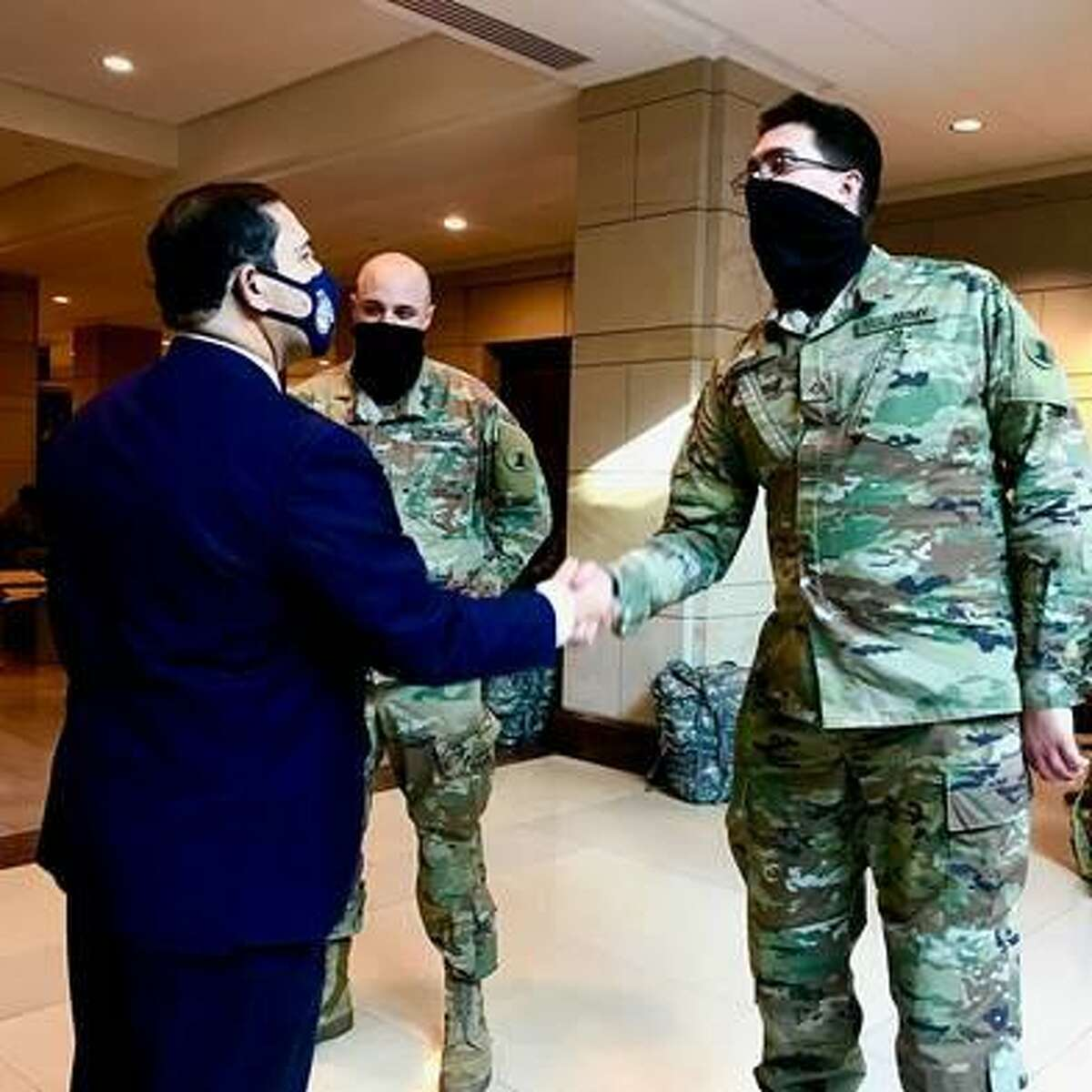 Rep. Henry Cuellar shakes hands with a National Guard member in the Capitol Visitors Center.
