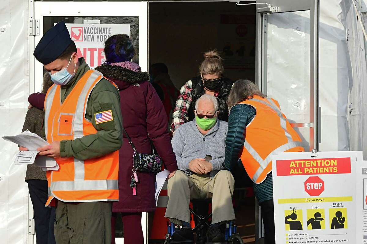 A man in a wheelchair is brought into a tent to receive the COVID-19 vaccine at University at Albany on Friday, Jan. 15, 2021 in Albany, N.Y. The mass-vaccine site opened today at this location. (Lori Van Buren/Times Union)