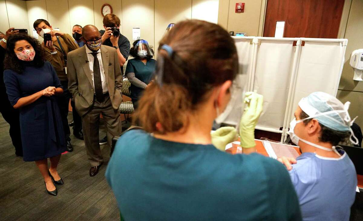 Harris County Judge Lina Hidalgo, left, Houston Mayor Sylvester Turner and others watch as Houston Methodist Hospital RN Kristin Adolphs prepares to give Nestor Esnaola, surgical director of cancer center, his COVID-19 vaccination at Houston Methodist Hospital Tuesday, Dec. 15, 2020 in Houston.