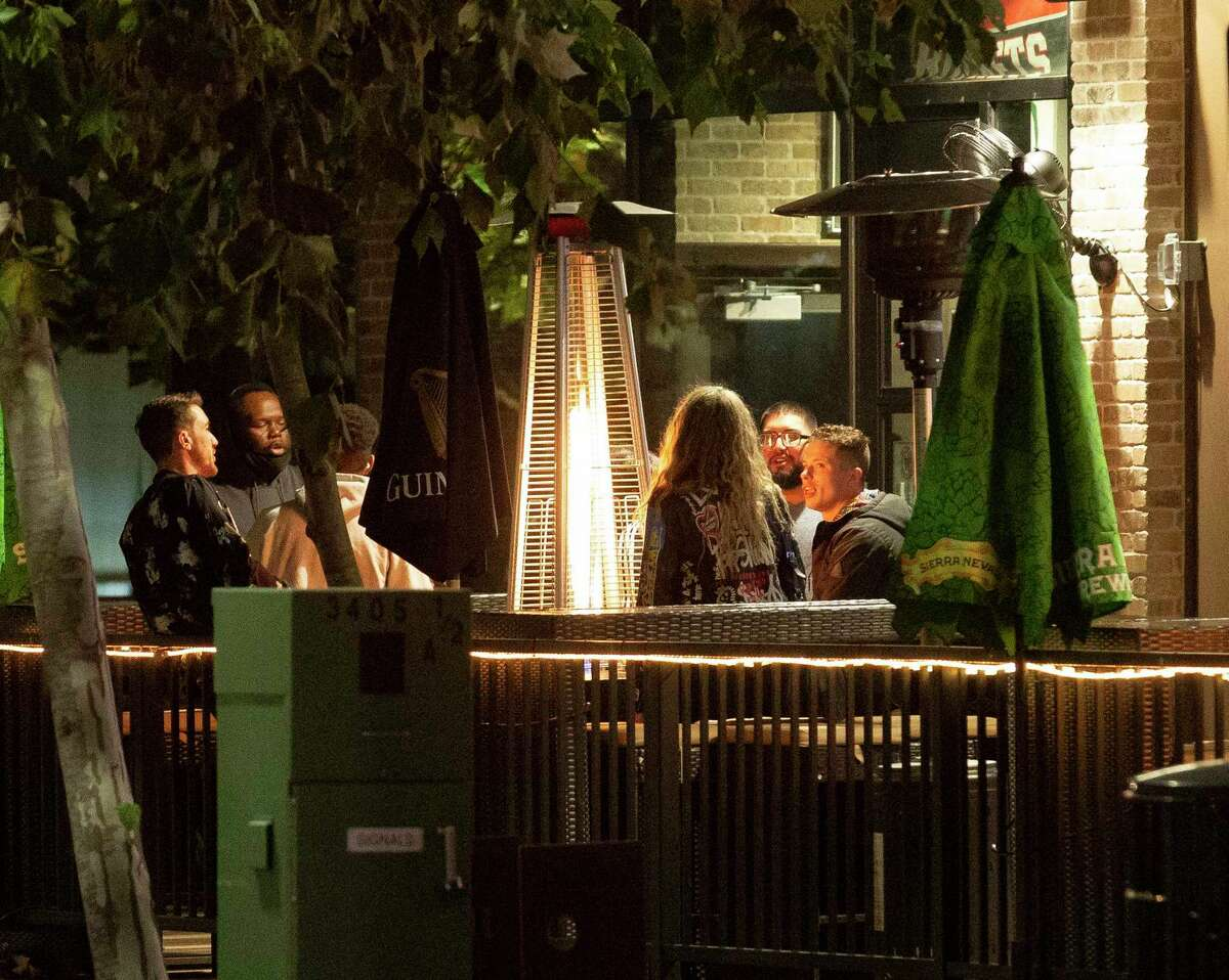 People hangout at a patio of a bar on Holman Street Thursday, Jan. 14, 2021, in Houston.