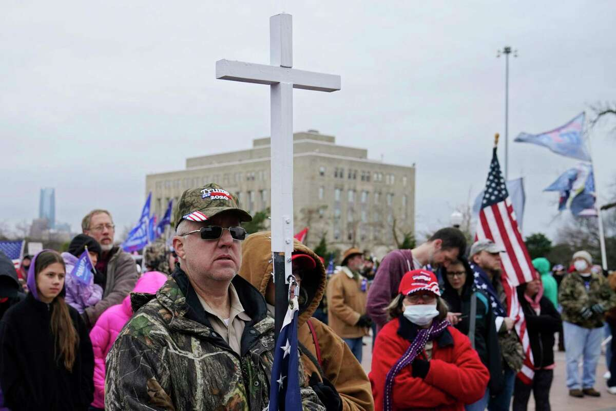 Kenny Womack, of Edmond, Okla., holds a cross at a Trump rally at the state Capitol, Wednesday, Jan. 6, 2021, in Oklahoma City. (AP Photo/Sue Ogrocki)