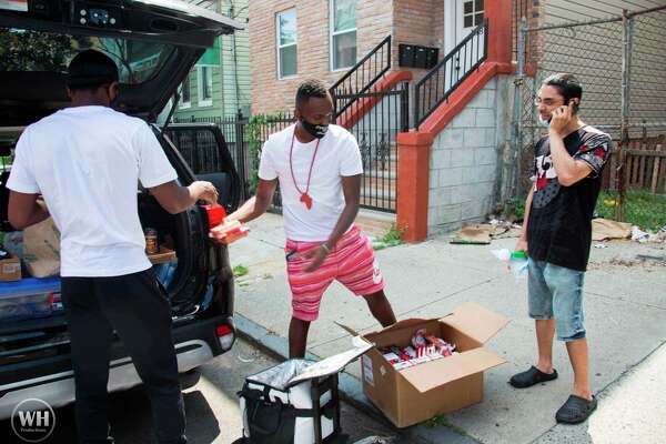 Byron Brooks (center) and another volunteer help pass out supplies during the For the Hood Tour. During the tour, Brooks traveled across the U.S. to provide necessary resources to those in need. (Courtesy photo)