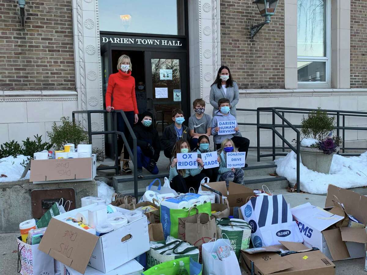 Diane Barston, program assistant, left, and Ali Ramsteck, director of Darien Human Services with all the donations and fifth grade students from Ox Ridge Elementary School.