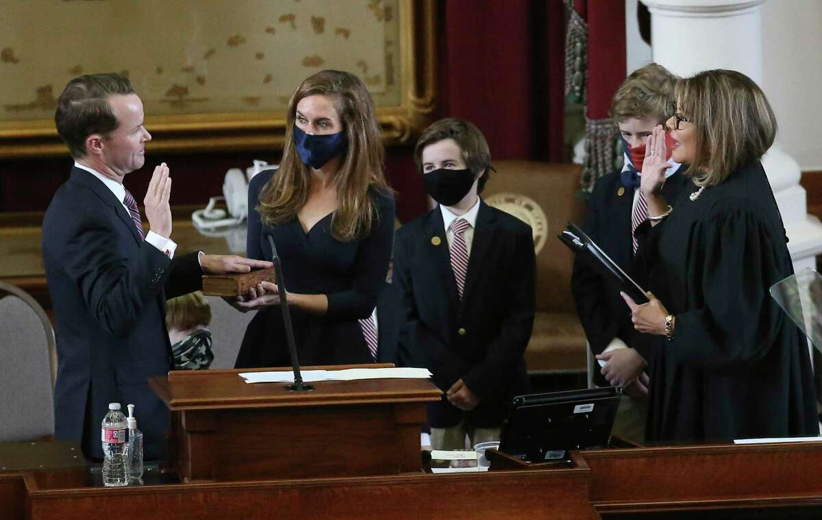 State Rep. Dade Phelan (left) takes the oath for Speaker of the House as his wife, Kim, holds the Bible with Texas Supreme Court Justice Eva Guzman (right) presiding over the oath during the convening of the 87th Texas Legislature in Austin on Tuesday, Jan. 12, 2021.