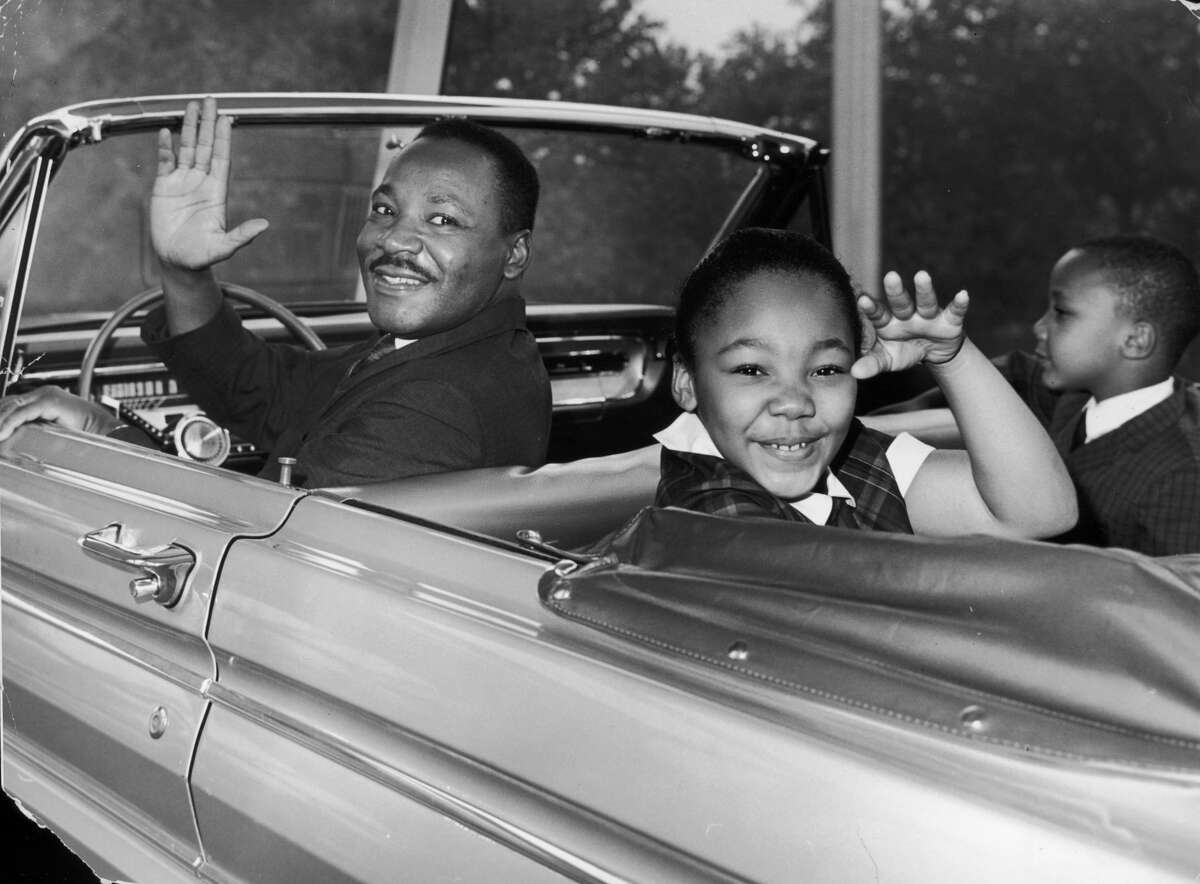 American civil rights leader Martin Luther King Jr. (1929 - 1968) waves with his children, Yolanda and Martin Luther III, from the 'Magic Skyway' ride at the Worlds Fair, New York City on Aug. 12, 1964.