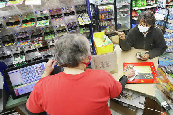 Bernadette Bridges, left, a morning clerk at the Shell Station located on the corner of Brown Street and Washington Avenue in Alton, takes a lottery order from a customer Friday. The Powerball drawing Saturday will be $640 million and Friday night's Megga Millions has grown to $750 million.