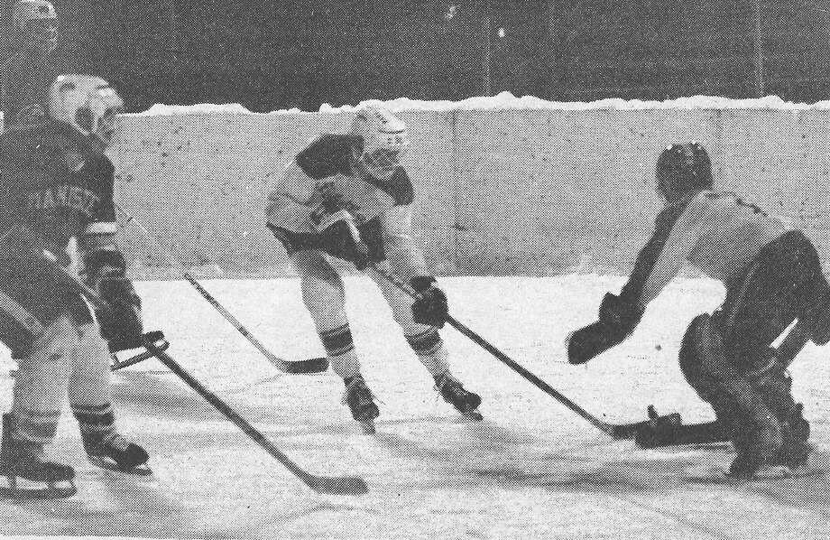 Jason Lewis (left) and Frank Moser attack the goalie during a power play in the skating rink in Sands Park this past week in 1981. (Manistee County Historical Museum photo)