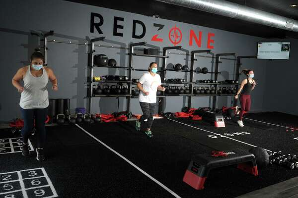 """RedZone members work out at a new fitness center in Weston, Conn., adhering to mask and distance rules in effect under Connecticut's """"2.1"""" safeguards to limit any transmission of COVID-19."""