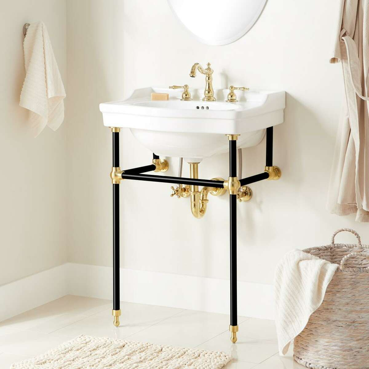 Today, homeowners are more willing to mix and match finishes, such as this standalone sink that combines matte black supports with polished gold hardware and fixtures.
