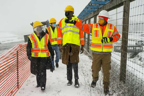State Rep. Annette Glenn, left, and Michigan Lt. Governor Garlin Gilchrist, center, chat with MDOT Construction Engineer Shaun Bates, right, as they tour the construction site of the temporary M-30 bridge over the Tobacco River Friday, Jan. 15, 2021. (Katy Kildee/kkildee@mdn.net)