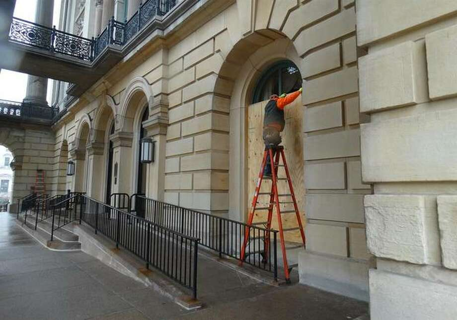 Crews place plywood over windows at the Capitol in Springfield on Friday amid FBI warnings of potential armed protests leading up to the inauguration of President-elect Joe Biden. Photo: Peter Hancock | Capitol News Illinois
