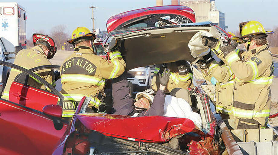 East Alton firefighters turned a Kia Rio into a convertible Tuesday morning in an effort to extricate the driver. The single-vehicle crash occured when the driver smashed into a guardrail on Illinois 143, east of the former power plant. Rescuers used a hydraulic rescue tools to cut the car's top off during the nearly hour-long rescue. Fire Chief Tim Quigley was inside the car with the driver, who was covered with a sheet.