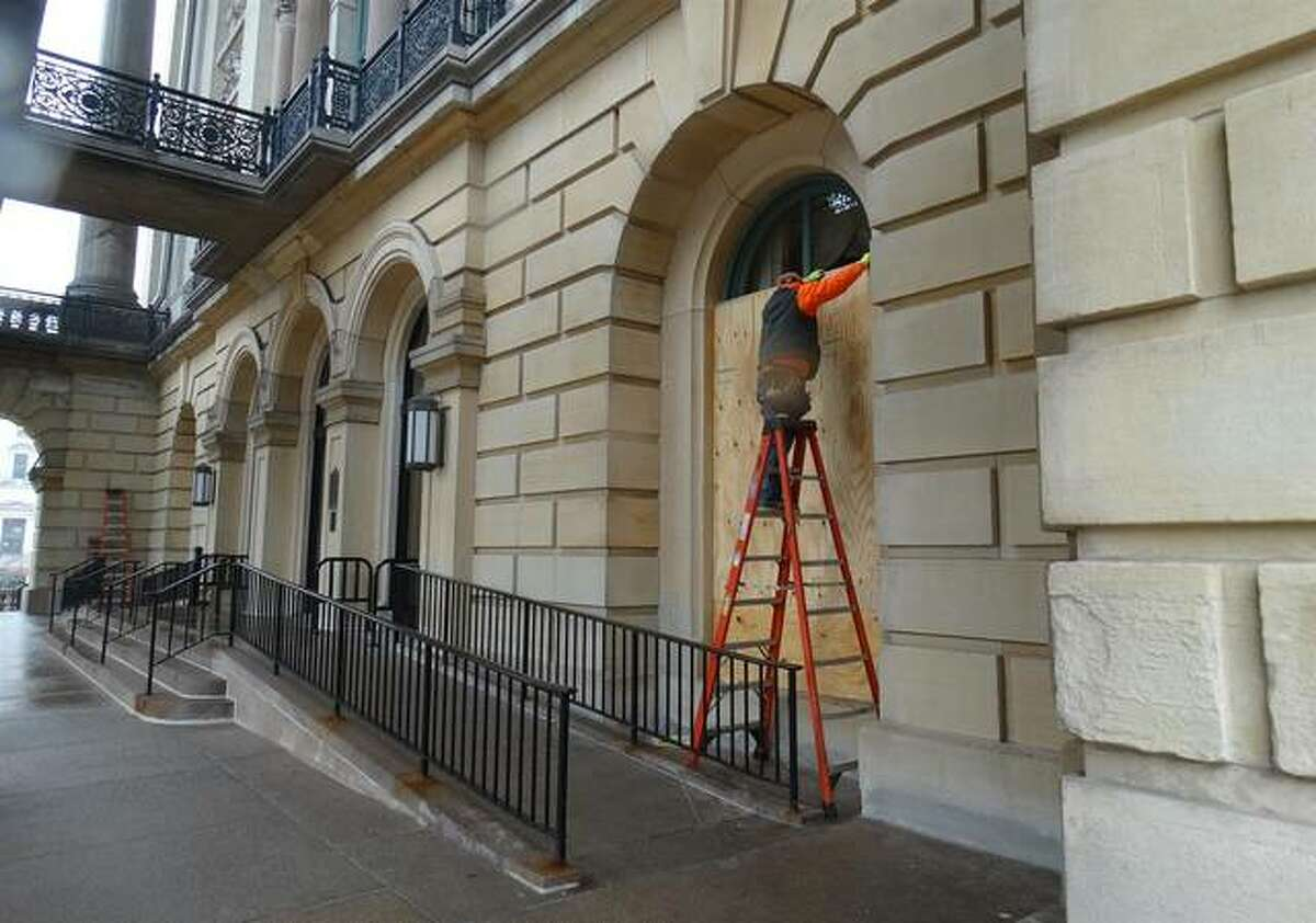 Crews place plywood over windows at the Capitol in Springfield on Friday amid FBI warnings of potential armed protests leading up to the inauguration of President-elect Joe Biden.
