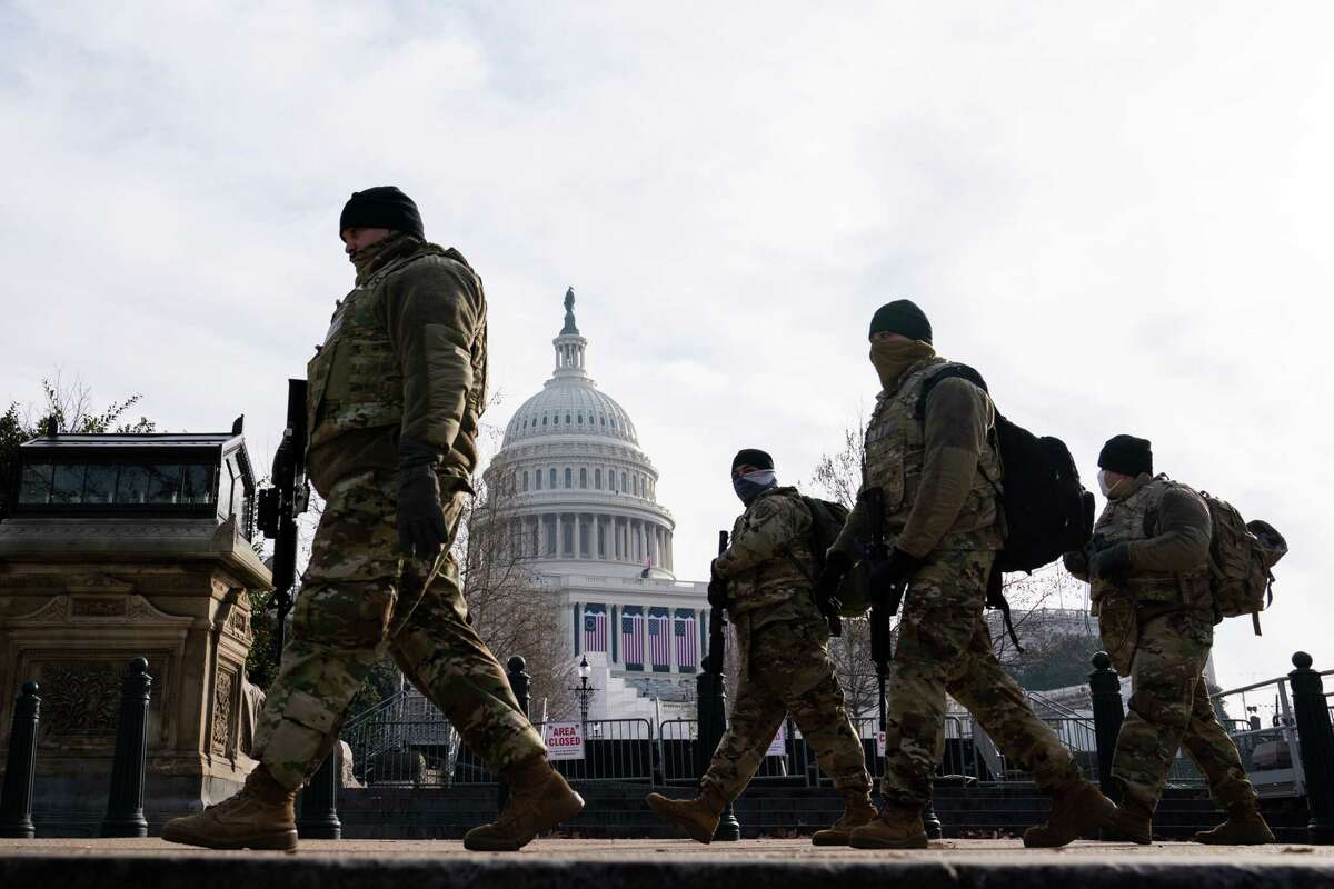 National Guard troops patrol the Capitol grounds in Washington on Friday, Jan. 15, 2021. The stage for Inauguration Day is in the background.