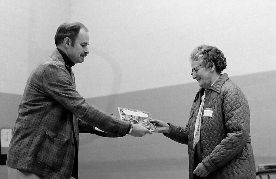 "Eva Densmore (right) receives a commendation from Ben Howells, Resource Forester for Packaging Corporation of America's Filer Mill, for her selection as ""Tree Farmer of the Year"" by the Manistee County Soil Conservation District's Board of Directors. Densmore received the award at the SCD's 35th annual meeting this past week in 1981 at the Kaleva School. (Manistee County Historical Museum photo)"