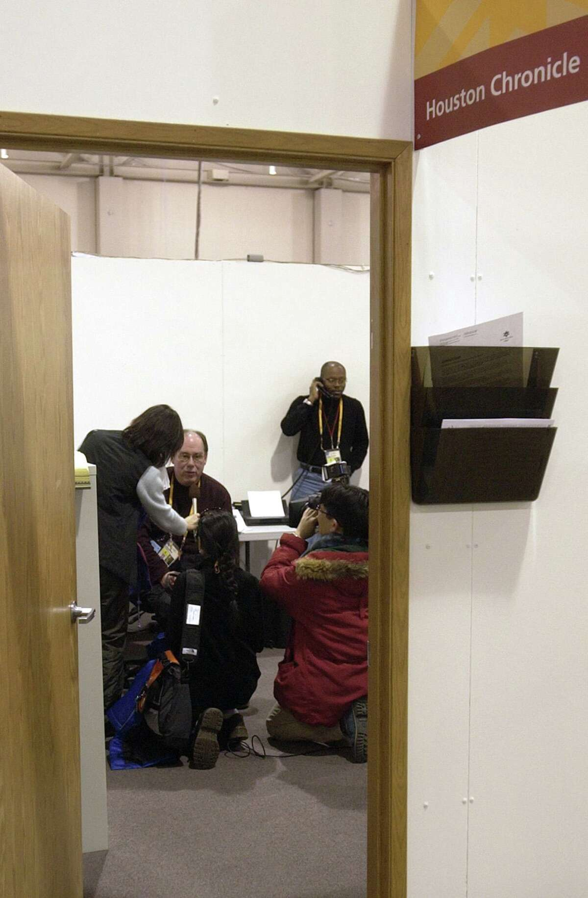Chronicle sportswriter Jerome Solomon answers a phone call, while Asst. Sports Editor David Barron is interviewed by a Japanese television crew in the Chronicle workspace at the Main Media Center on the eve of the 2002 Olympic Winter Games in Salt Lake City on Thursday, Feb. 7, 2002.