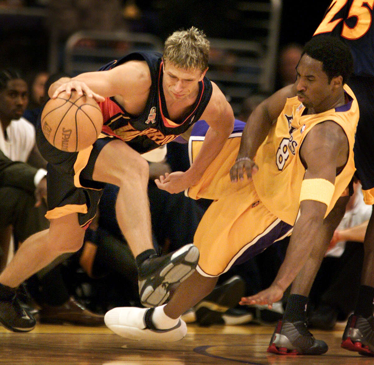 Laker Kobe Bryant gets knocked to the ground while guarding Golden State Warrior Bob Sura in the first half at Staples Center on Dec. 16, 2001.