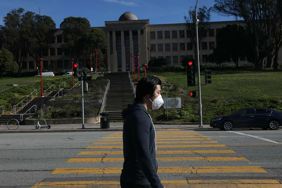 Jack Wu of San Francisco walks past the Science Hall at City College of San Francisco on Friday, January 15, 2021 in San Francisco, Calif. San Francisco will soon open three large vaccination sites around the city, one of which will be located at City College's main campus.