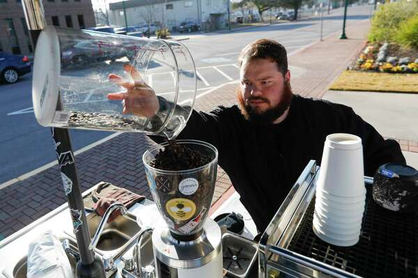Bradley Bailey, owner of Galavants Coffee, restocks coffee beans at the corner of Metcalf Street and North Main Street, Wednesday, Jan. 13, 2021, in Conroe