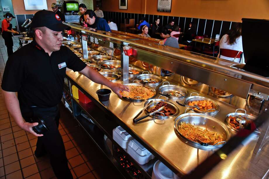 """Jesse Hernandez reaches out for a pair of tongs as he prepares a plate of chinese food on Monday afternoon at Panda Express as the chain restaurant participates in the """"Together we're feeding America"""" project. The Laredo Panda Express will donate part of its proceeds to the South Texas Food Bank. Photo: Danny Zaragoza, Staff Photographer / LAREDO MORNING TIMES"""