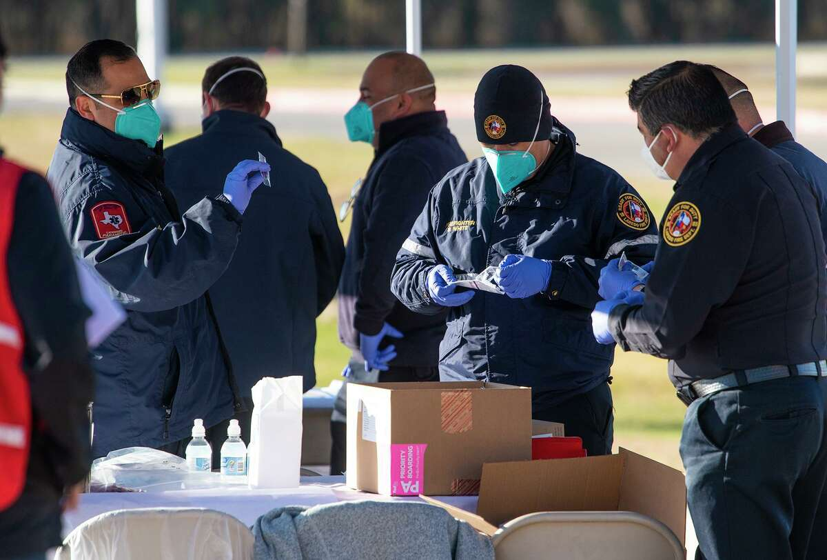 First responders and nurses fill syringes as they help distribute the Moderna Covid-19 vaccine to workers in the medical field, Saturday, Jan. 2, 2021 at TAMIU.