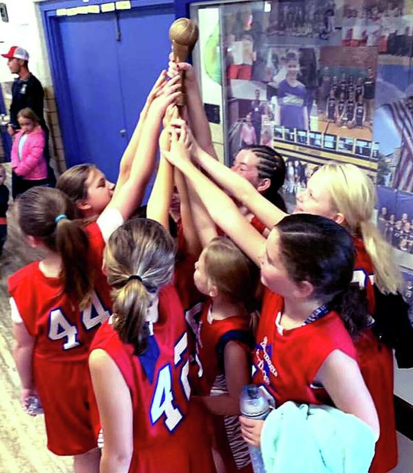 Members of a St. Ambrose School girls basketball team celebrate after a 2019 tournament win. St. Ambrose in Godfrey, as well as other area public and parochial elementary schools, junior highs and middle schools are in an athletics pause just like their high school counterparts. Photo: File Photo