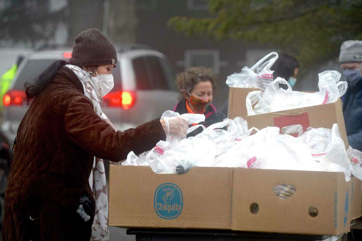 Volunteer Anita McKean, of Ridgefield, picks up bags of food to be given away as the Connecticut Food Bank returned to St. Andrew's Church on Friday after stopping for months due to the pandemic. The church has been the site for the food bank's mobile food pantry for several years, coordinating the monthly food delivery with the Connecticut Food Bank and the town's social services department. Friday morning, January 15, 2021, in Ridgefield, Conn.
