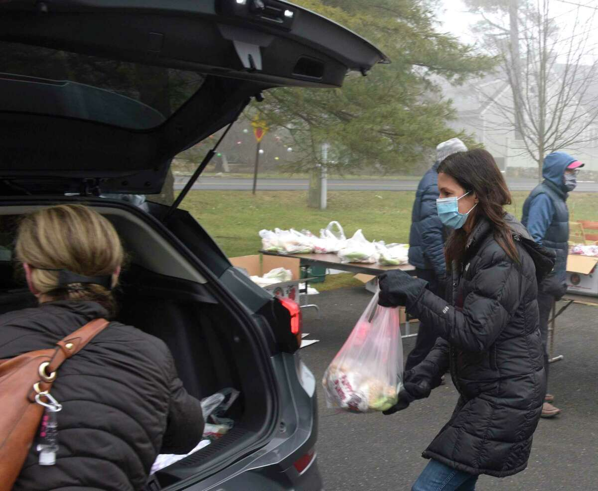 Volunteer Elizabeth Butler, of Ridgefield, puts a bag of food into the back of a car as the Connecticut Food Bank returned to St. Andrew's Church on Friday after stopping for months due to the pandemic. The church has been the site for the food bank's mobile food pantry for several years, coordinating the monthly food delivery with the Connecticut Food Bank and the town's social services department. Friday morning, January 15, 2021, in Ridgefield, Conn.