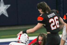 Aledo running back Sammy Steffe (26) comes over to embrace Crosby cornerback Jonathan Fuselier (19) and inside linebacker Coby Riendeau (33) as they react to their loss in the Class 5A Division II UIL State Championship high school football game at AT&T Stadium Friday, Jan. 15, 2021, in Arlington, Texas. Aledo captured the title with a 56-21 win over Crosby.