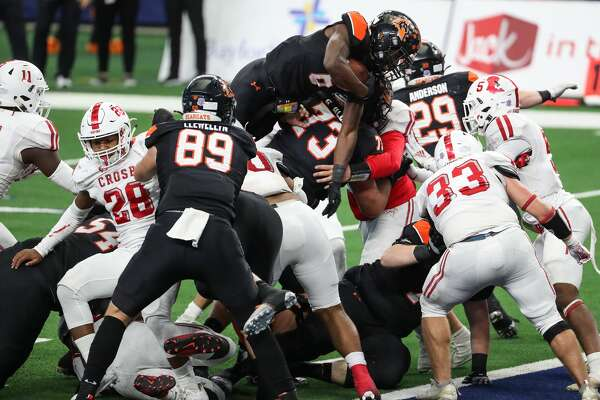 Aledo running back Demarco Roberts (6) leaps over the Crosby defense for a 1-yard touchdown run during the second half of the Class 5A Division II UIL State Championship high school football game at AT&T Stadium Friday, Jan. 15, 2021, in Arlington, Texas. Aledo captured the title with a 56-21 win over Crosby.