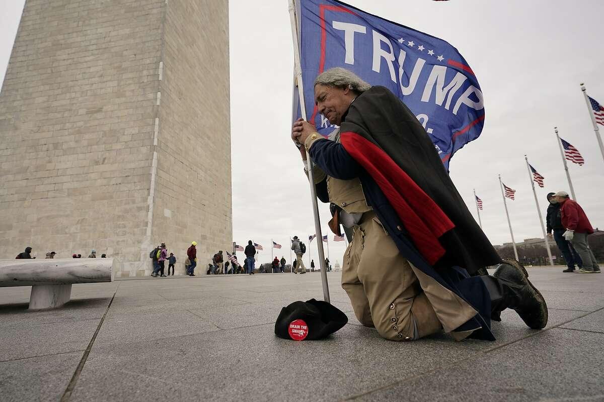 A man dressed as George Washington kneels and prays near the Washington Monument with a Trump flag on Jan. 6.