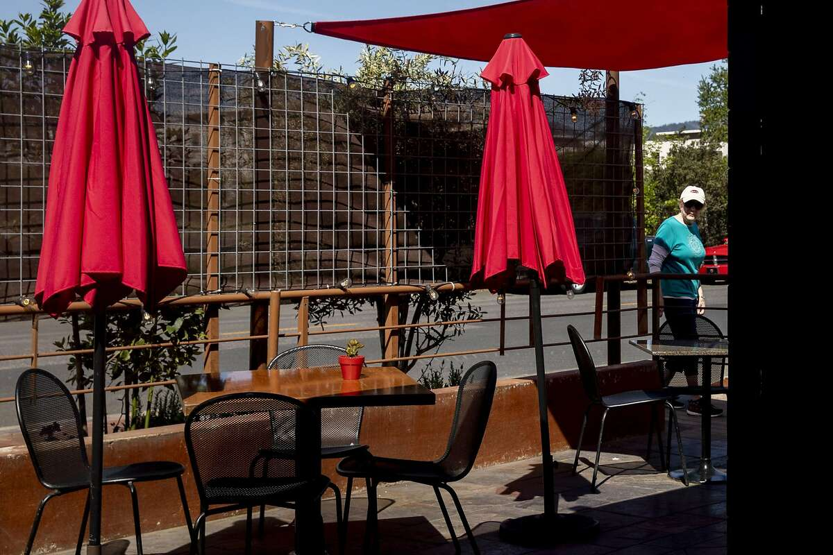 A woman peeks at outdoor seating set up outside of Fume Bistro in Napa in May 2020. Fume is among more than 50 businesses suing Gov. Gavin Newsom to bring back outdoor dining.