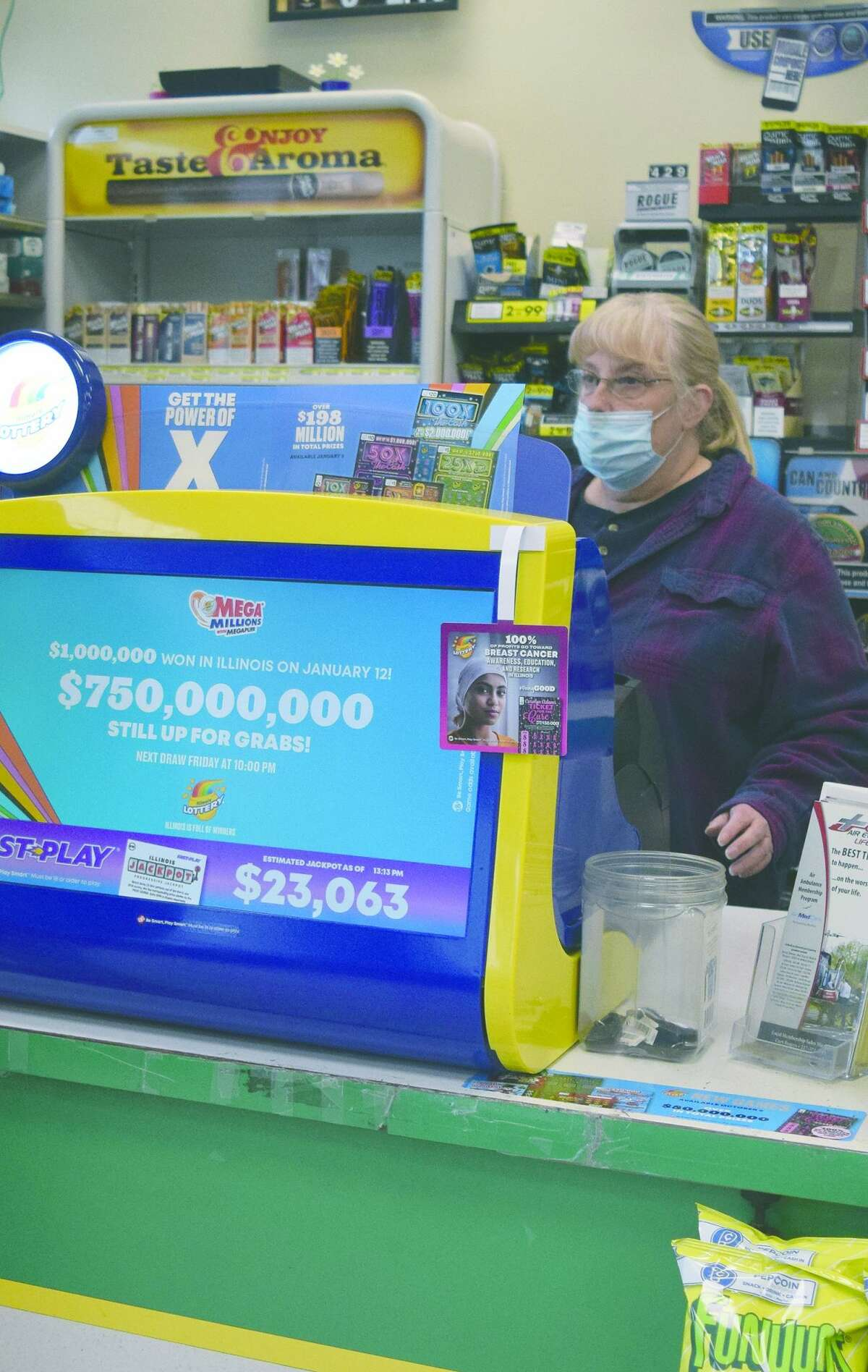 Cindy Walker, manager at Ayerco Convenience Center at 1204 W. Walnut St., works the register Friday. On Saturday, those with a ticket will have a chance to win a $640 million Powerball prize, the game's eighth-largest jackpot.
