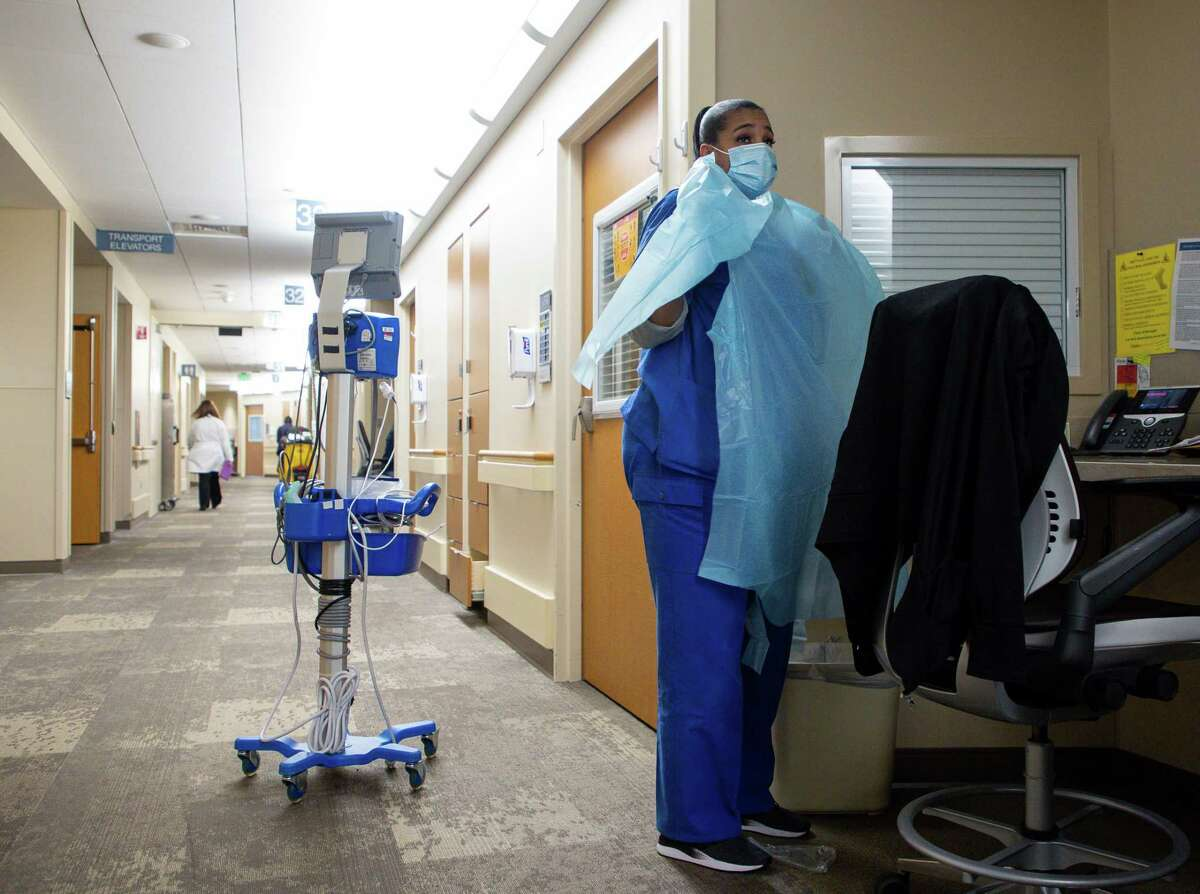 Darrelyn Mathieu, patient care assistant, wears a plastic gown before entering a patient's room in the cardiovascular acute care unit, at Houston Methodist Debakey Heart and Vascular Center on Thursday, Jan. 14, 2021, in Houston. Texas hospitals, already facing an increase in patients brought by the pandemic, is dealing with poached nurses. Seven months after hospitals competed for ventilators, personal protective equipment and COVID-19 test, nurses have become the hot commodity, desperately needed around the country.