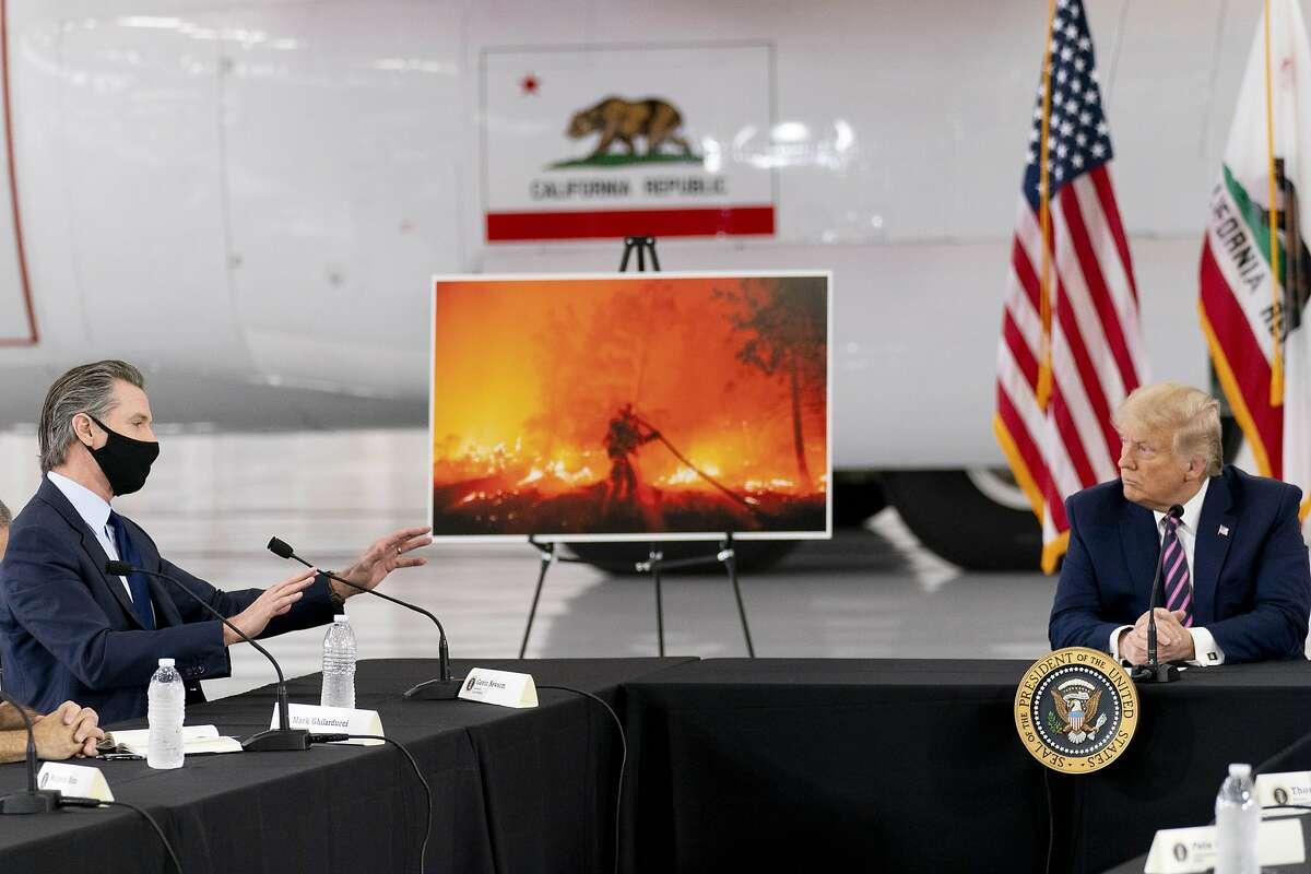 """Gov. Gavin Newsom (left) briefs Trump on the state's wildfires during the president's September visit to Sacramento. Trump rolled back environmental protections and blamed California's catastrophic wildfires on """"many years of leaves and broken trees."""""""