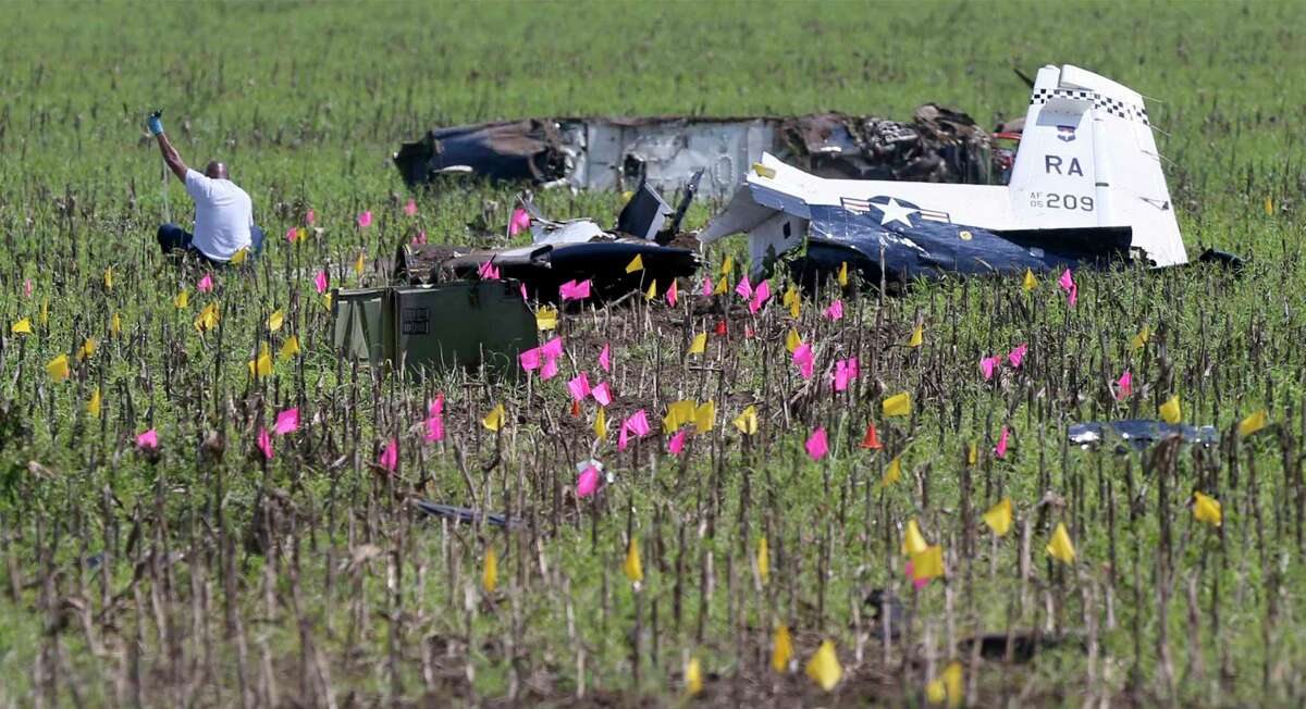 A person works Sept. 19, 2018 near the remains of a 12th Flying Training Wing two-seat, turboprop T-6A Texan II. The airplane crashed in a field near the intersection of Nacogdoches and Evans Roads after both pilots ejected safely. No one on the ground was hurt.