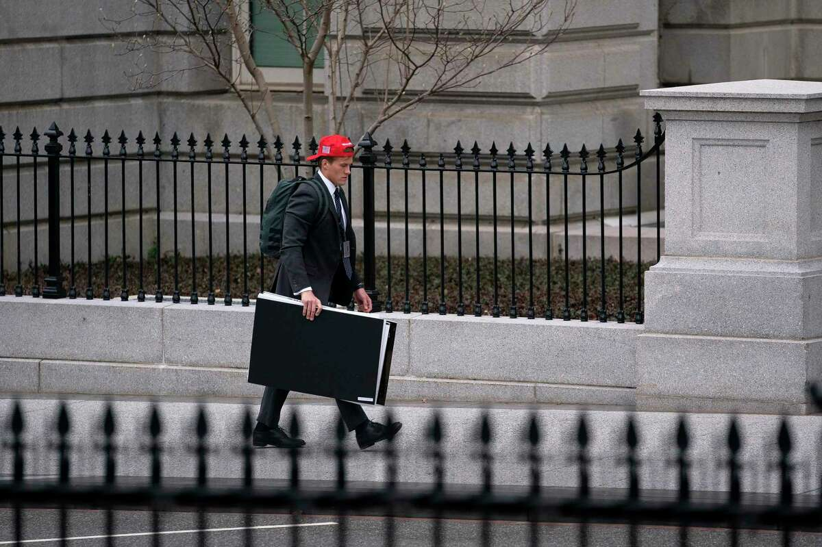 A staff member in a Trump hat departs the Eisenhower Executive Office Building in Washington, Jan. 15, 2021. House Speaker Nancy Pelosi said on Friday that the House managers she appointed to prosecute Trump's impeachment case were preparing to take their charge to trial in the Senate.(Stefani Reynolds/The New York Times)