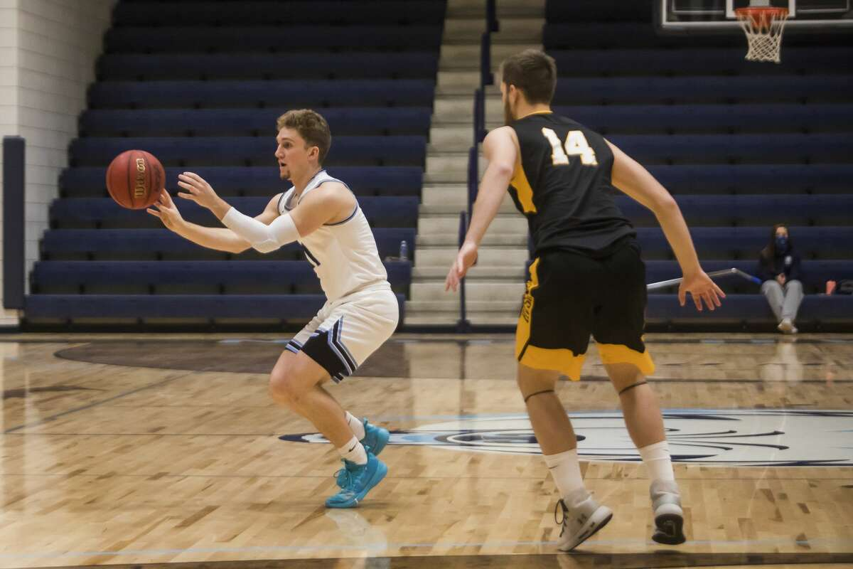 Northwood's Jack Ammerman passes the ball to a teammate during the Timberwolves' game against Michigan Tech Friday, Jan. 15, 2021 at Northwood University. (Katy Kildee/kkildee@mdn.net)