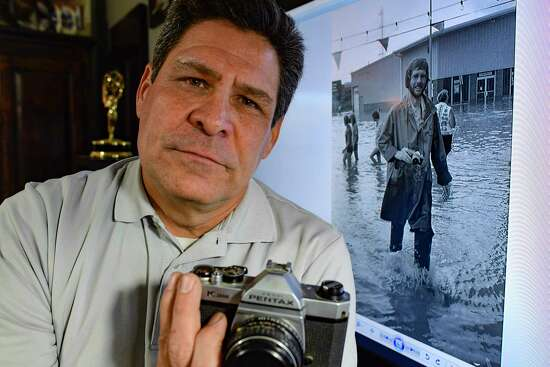 Brian Collister holds his father's Pentax camera, which his father used as a news photographer in New York in the 1960s. The photo in the background is of his father covering a flood.