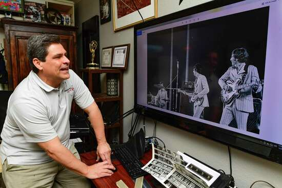Brian Collister enjoys a picture shot by his father, Bob Collister, of the Beatles' 1966 concert at Shea Stadium in New York. Brian Collister recently discovered many of his father's photos and negatives, which include pictures of NFL football games and many other news events.