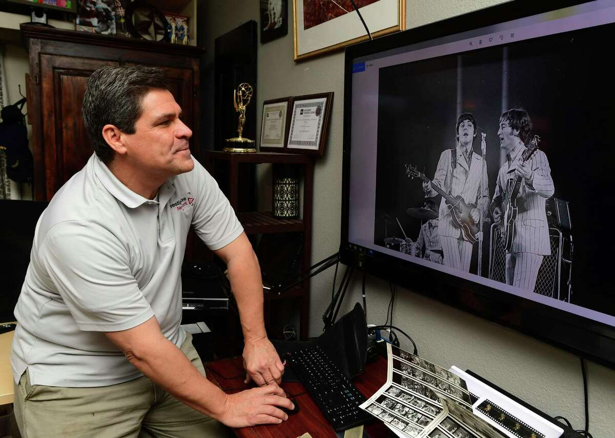 Brian Collister enjoys a picture that was shot by his father, Bob Collister, of the Beatles' 1966 concert at Shea Stadium in New York. Brian Collister recently discovered many of his father's photos and negatives, which include pictures of NFL football games and many other news events.