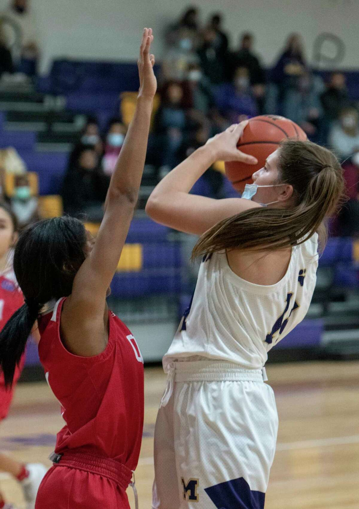 Midland High's Shelby Stephens pulls up for a shot over Odessa High's Kiki Lide 01/15/2021 at the Midland High gym. Tim Fischer/Reporter-Telegram