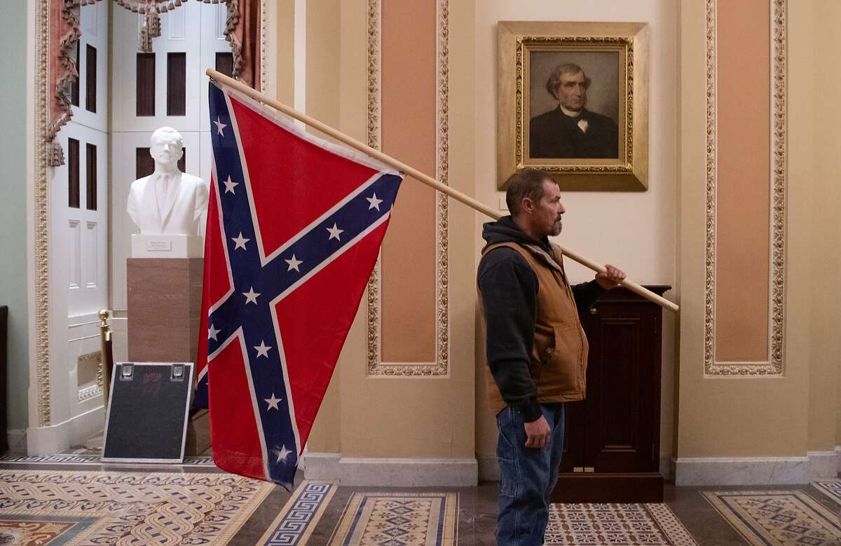 A Trump supporter with a Confederate flag outside the Senate Chamber during the Capitol riot.