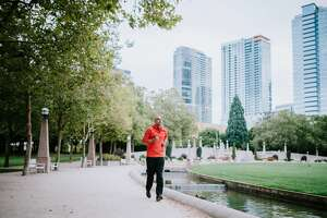 A man goes for a morning run through Bellevue's Downtown Park, a perfect place for a jog or other exercise with open footpaths and city skyline views.