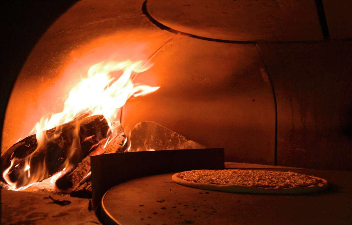 A pizza cooks in the wood fired oven at Andiamo Wood-Fired Pizza in Candlewood Lake Plaza in Brookfield, Conn. Friday January 15, 2021.