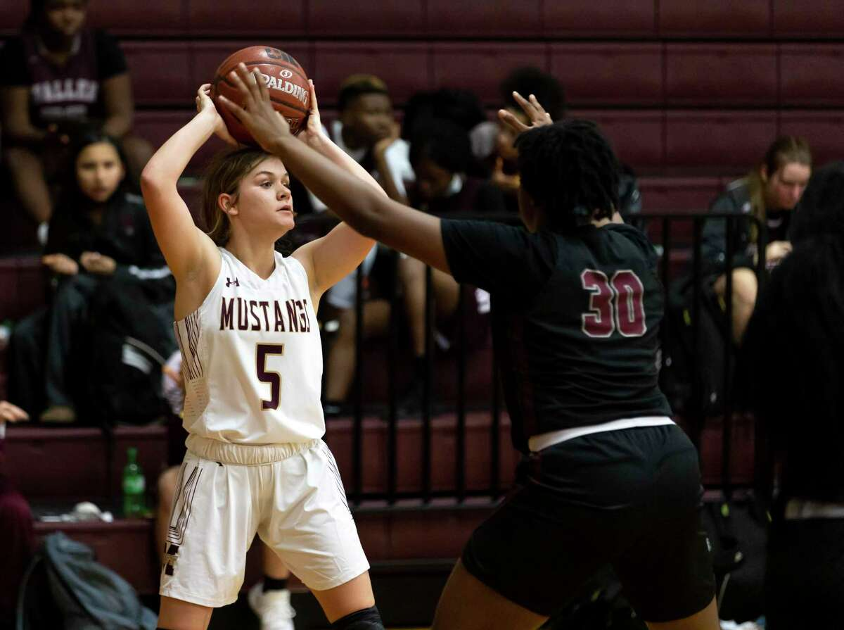 Magnolia West shooting guard Alivia Kiser (5) looks for an opening to pass the ball while under pressure from Waller shooting guard Kailyn Peters (30) during the first quarter of a District 19-5A girls basketball game at Magnolia West High School, Friday, Jan. 15, 2021, in Magnolia.