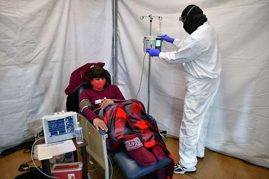 Rosalinda Espinoza, 58, receives an infusion of antibodies to battle COVID-19 at the Freeman Coliseum complex on Friday, Jan. 15, 2021. The infusion center is one way to avoid sending more patients to hospitals, which are close to being overloaded because of the coronavirus pandemic. Photo: Billy Calzada /Staff Photographer / `