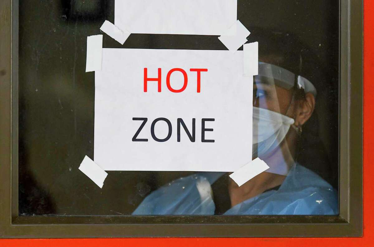 A nurse is seen in a window behind a door with signs warning that protective gear against the coronavirus is required to enter at the Freeman Coliseum complex on Friday, Jan. 15, 2021. San Antonio's health care system is in crisis from the latest COVID surge, and hospitals and local officials are doing everything they can to prevent th crisis from becoming a disaster.
