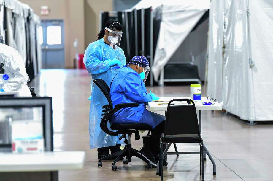 Medical personnel sort through information at the Freeman Coliseum complex on Jan. 15, 2021, where COVID-19 patients were being given infusions of antibodies. Photo: Billy Calzada /Staff Photographer / `